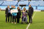 Miembros de la Fundación Aspace con Christian Lapetra en el terreno de juego durante el Partido del Real Zaragoza y al Apoel FC de Nicosia, sujetando el cheque con el 50% de la recaudación del partido.