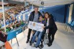 Miembros de la Fundación Aspace en las gradas de la Romareda en el Partido del Real Zaragoza y al Apoel FC de Nicosia sujetando el cheque del 50% de la recaudación del partido.