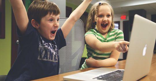 Niños celebrando delante de un ordenador